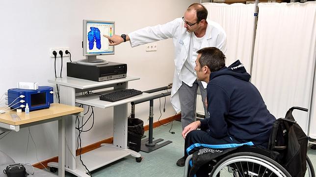 Un lesionado medular escucha atentamente las explicaciones de un médico sobre úlceras