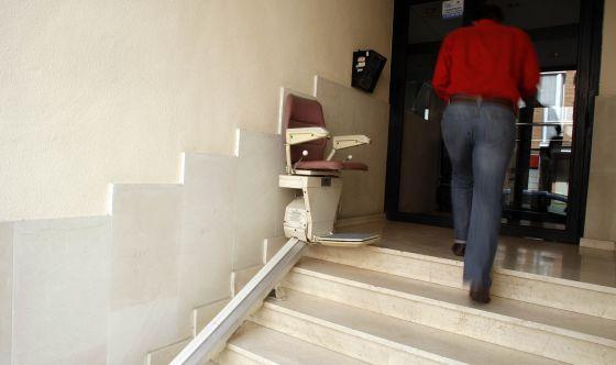 Silla mecánica para salvar las escaleras instalada en el acceso a una finca en Madrid. / Luis Sevillano
